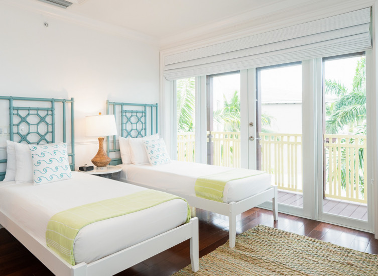 Room with two twin beds with aqua bed frames and door leading to balcony