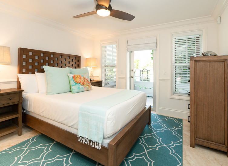 Room with double bed, wooden bed frame & aqua rug