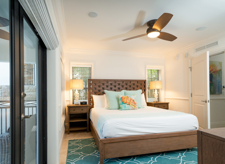 Room with double bed, aqua rug & fish throw pillows