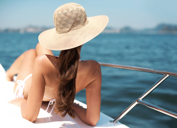 woman laying on boat deck sun bathing in white swimsuit and sun hat