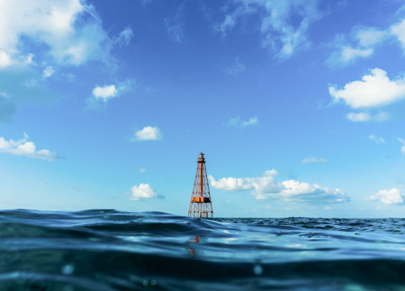 a red buoy in ocean water against a cloudy blue sky