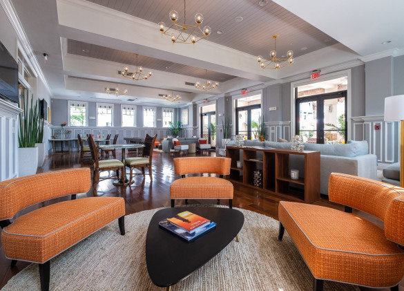 clubhouse with curved orange couches around a table with seating in background