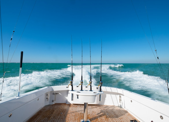 rear deck of a fishing boat with fishing poles looking out at the wake and blue green ocean