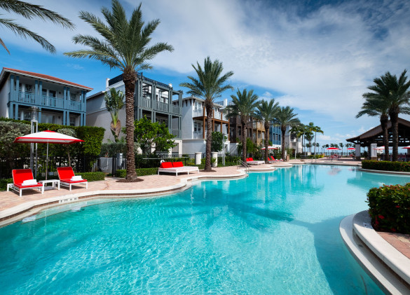 pool area with crystal blue water and palm trees with vacation homes in background
