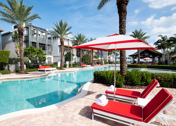 red chaise lounge and red and white umbrella on stone patio next to crystal blue pool