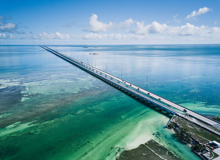 aerial view of the seven mile bridge with green blue water and blue sky