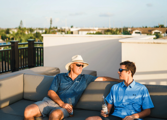 two men relaxing on outdoor patio furniture enjoying conversation