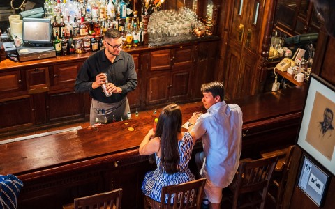 Couple seated at bar in front of bar tender