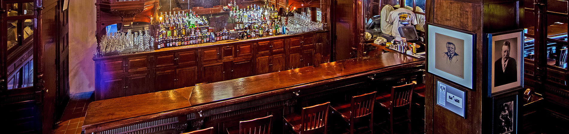 a large wood bar with wood barstools