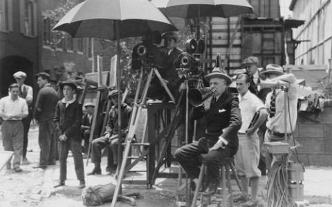 old black and white photo of a movie director on set