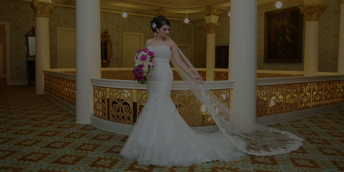 a woman in a wedding dress holding a bouquet of flowers inside the hotel