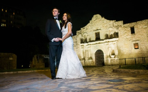 a couple standing outside of a stone building in their wedding attire