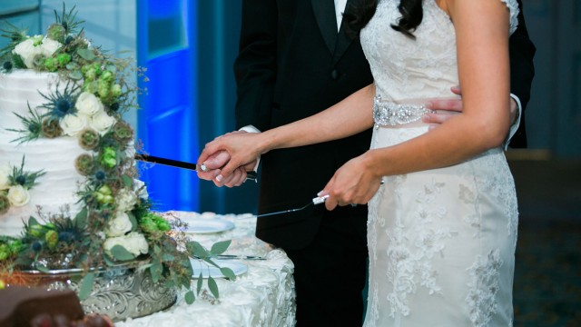 a married couple cutting a cake with flowers on it