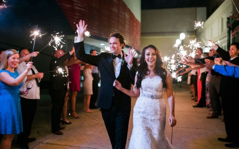 a just married couple walking past people holding sparklers