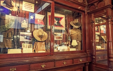 a glass casing of vintage western clothes and memorabilia
