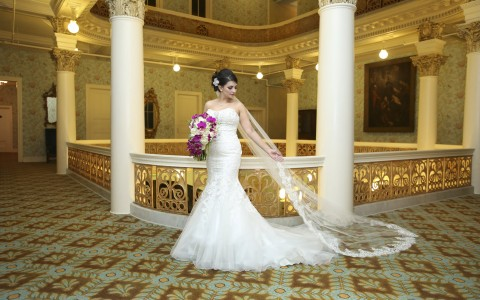a woman in a wedding dress holding a bouquet of flowers in the hotel