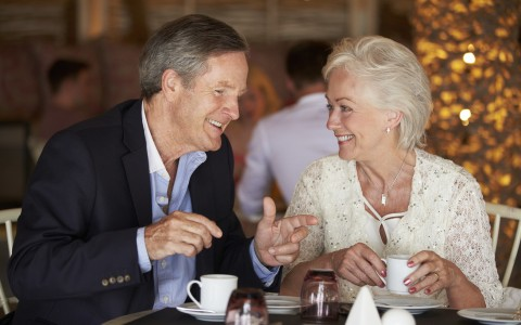 mature couple enjoying cups of coffee at dinner