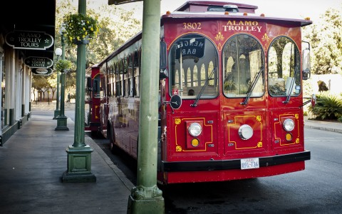a vintage red trolley parked out front of the menger hotel