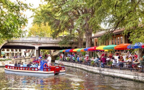 view of the river with a group of people enjoying a boat tour, people on the bank enjoying meals under colorful umbrellas