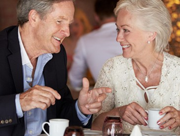 a mature couple enjoying cups of coffee at dinner