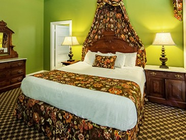 bed with floral accents, two nightstands with lamps, dresser with a mirror