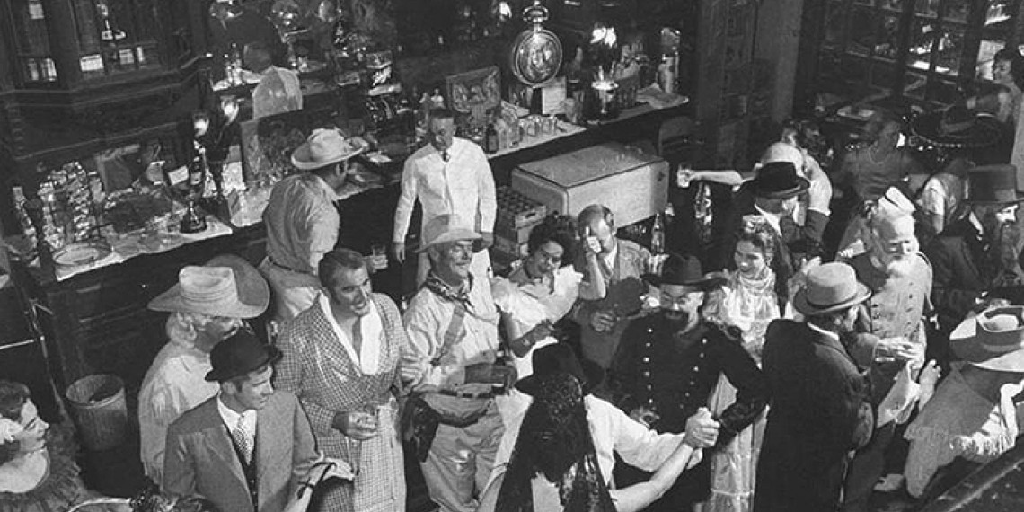 black and white photo of a group of people mingling in a bar