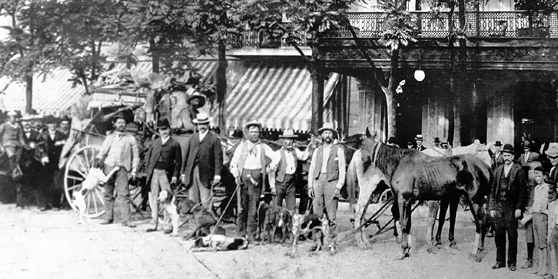 black and white photo of a group of men lined up on a street with horses