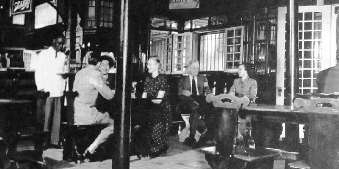 black and white photo of people enjoying cocktails in a bar
