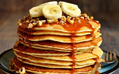 stack of pancakes with nuts and bananas on top