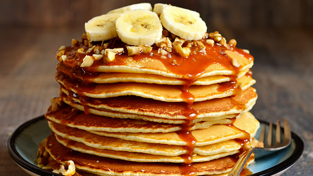 stack of pancakes with nuts and banana's on top