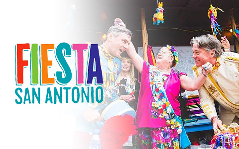 Two older gentleman and a woman in the center in brightly colored clothing dancing and celebrating. A pinata is visible in the background. Overlaid on the image reads Fiesta San Antonio.