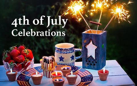 Strawberries in a bowl, Candles on a plate painted with American flags, a blue and white mug with two stars and a container holding three sparklers on a white table outside. On the image reads 4th of July Celebrations.