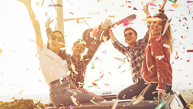Two guys and two girls sitting on top of car with their hands up, and confetti is flying around