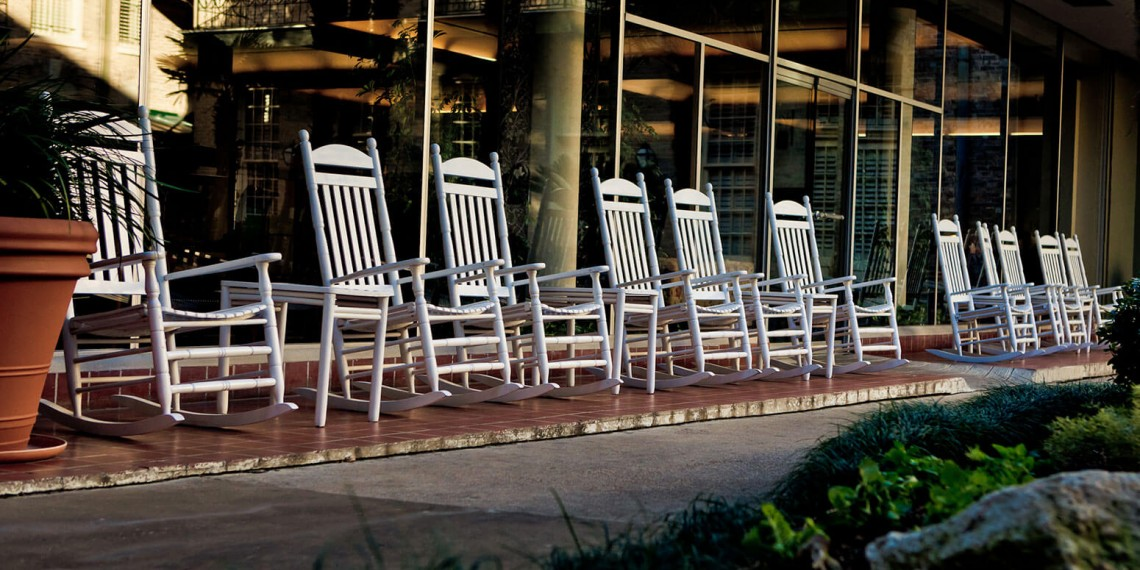 row of white rocking chairs set up outside