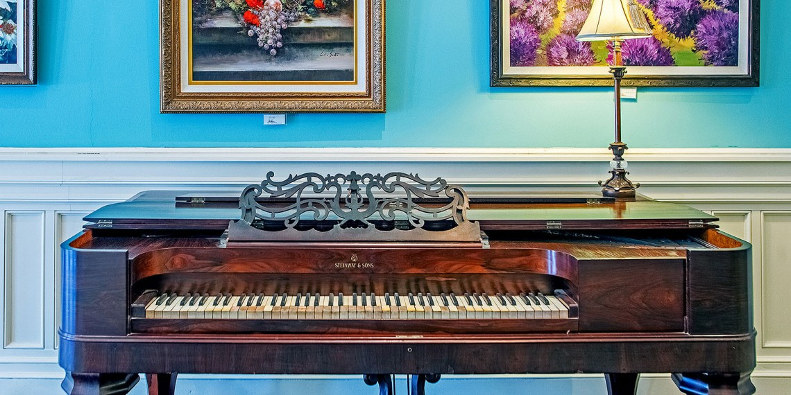 blue room with a piano, paintings on the walls