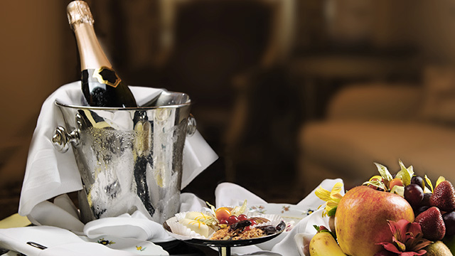 a bottle of champagne being chilled in an ice bucket next to a plate of fruit