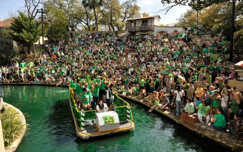 a boat going down a green colored waterway while a crowd watches