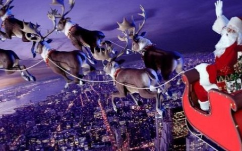 Santa in the sky on his sleigh being pulled by reindeers