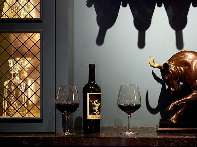 bottle of wine, two glasses of red wine, bull statue