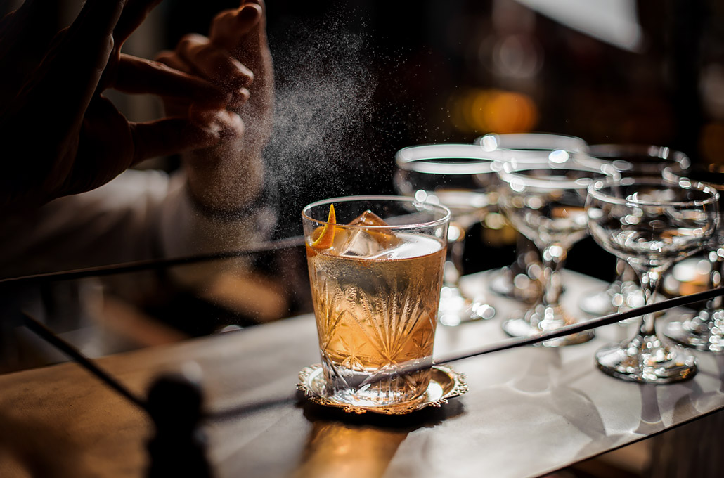 bartender finishing off a poured cocktail