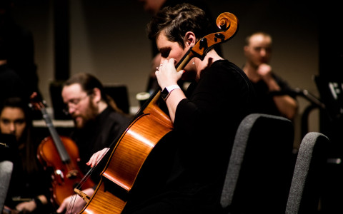 Concert Cellist dressed in black with the rest of the ensemble in the background