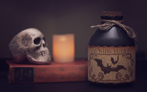 Spooky potion bottle book by Edgar Allan Poe candle and skull