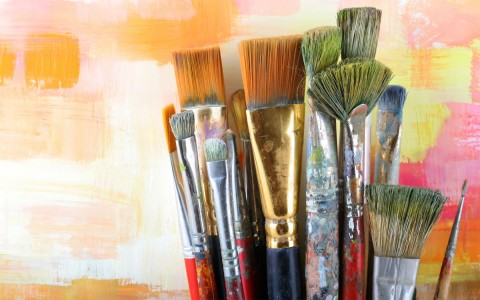 set of paint brushes that have been heavily used