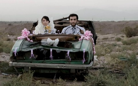 bride and groom sitting in dilapidated car decorated for a wedding