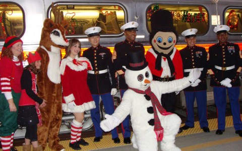 Soldiers in full formal garb posing for a photo with christmas mascots