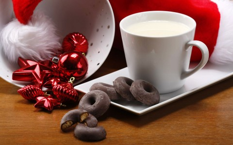 glass of milk with small donut shaped cookies and Christmas decorations on a table