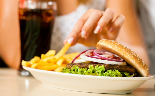 plate of burger and fries and a soda pop being picked at by a women