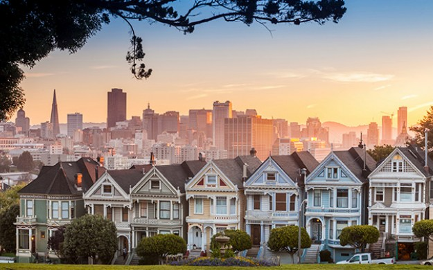 painted ladies houses line a street during sunset