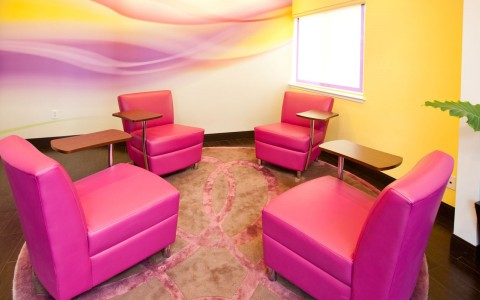 Small meeting area is a circular room with 3 read lounge chairs ad desks attached. Colorful wall paper and small window