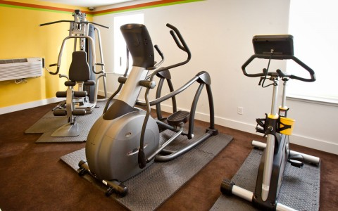 fitness center containing an elliptical, spin bike, and cross training weight machine